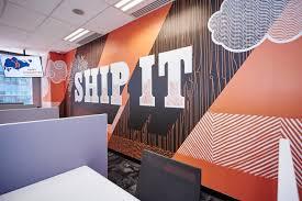 """Mural laranja que diz """"ship it"""" em uma parede no escritório da HubSpot em Singapura"""