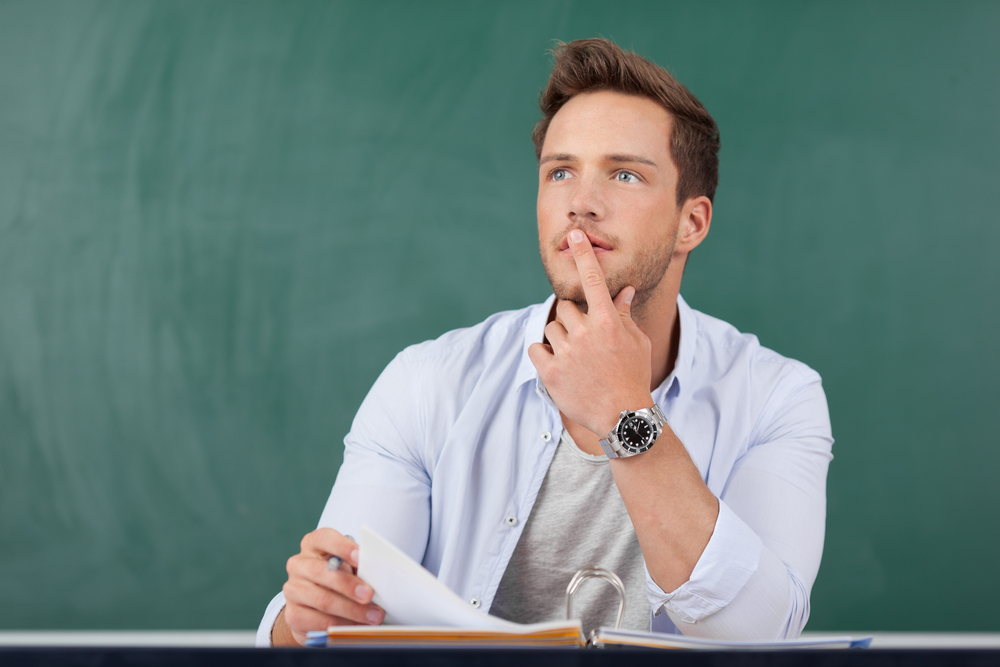 Thoughtful young man sitting with book in front of chalkboard